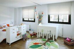 Weisse Möbel und farbige Elemente wie ein runder Teppich mit stilisiertem Baummotiv in modernem Kinderzimmer