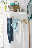 A homemade rope hand towel holder in a white bathroom with wood panels