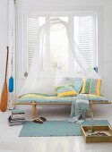 A wooden lounger with striped upholstery and a mosquito net in front of a window in a light living room