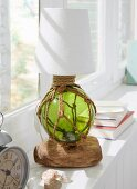 A handmade table lamp with a stand made from a fishing net and driftwood