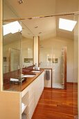 Designer bathroom - fitted washstand with white base units and glass shower cubicle below skylight
