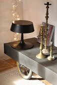 60s-stlye table lamp with black lampshade and tulip base and brass candlesticks on metal table on wheels