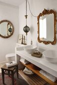 Rustic wooden stool in front of white washstand with twin basins below vintage mirror with ornate gilt frame