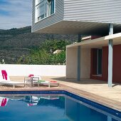 Contemporary house with aluminium cladding and sun loungers on wooden deck surrounding pool