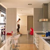 White designer kitchen with pale grey wall tiles, open doorway with view of woman walking down staircase in living room
