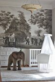 White cradle with fabric canopy, elephant toy and mural with elephant motif in nursery with colonial ambiance