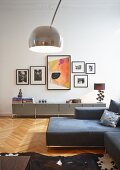 Arc lamp, grey sofa combination and grey, USM Haller, modular sideboard below collection of pictures