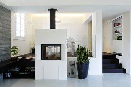 Freistehender, gemauerter Kamin und Pflanzentopf vor Empore mit Essplatz, in modernem Wohnzimmer