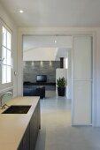 Küchenzeile am Fenster, vor offener Schiebetür und Blick ins moderne Wohnzimmer