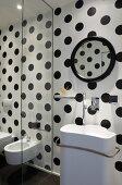 Designer washbasin on black and white polka dot wall; glass panel screening bidet and toilet