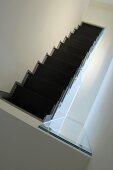 Blick von oben auf schwarze Treppe in weissem, minimalistischem Treppenhaus