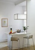 Designer bar stools at counter with white stone counter below cubic pendant lamp in minimalist interior