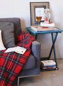 Tartan blanket on couch next to glass of wine and stacked books on folding table