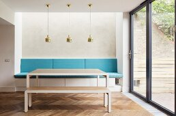 Modern table and matching bench in front of masonry bench with blue cushions below row of brass pendant lamps