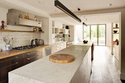 Long concrete kitchen counter under rod-shaped pendant lamps opposite kitchen counter with gas cooker