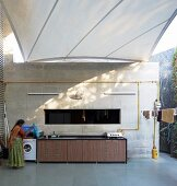 Awning shading spacious terrace; woman standing next to washing machine in outdoor kitchen counter