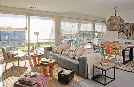 Sunny interior; lounge area with armchairs, pale grey sofa, small wooden side tables and dining area in background