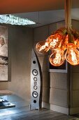 Bundle of light-bulb pendant lamps in front of extravagantly shaped speaker