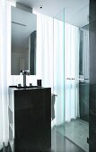 Column washstand with mirror suspended from ceiling and shower cubicle in front of glass wall with curtain