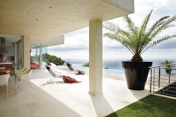 Designer dining area below projecting concrete roof and sun loungers on pool terrace of modern holiday home by the sea