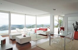Designer interior with plexiglas furniture and view of landscape through glass wall