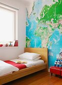 Single bed with wooden frame against wall with wallpaper map of world in child' bedroom