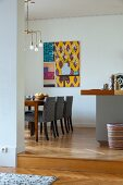 Grey-covered chairs around table below Art-Deco pendant lamp in dining room with modern artwork on wall