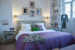 Purple cover on double bed with wooden headboard below framed photos on wall