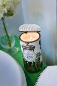 Lit scented candle in vintage-style holder