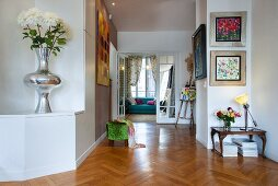 Herringbone parquet floor, tall silver vase of chrysanthemums and open double doors in background in hallway of period apartment