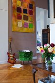 Vase of roses on antique side table and green velvet pouffe below modern artwork on painted wall