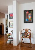 Patterned cushions on antique chair below modern artwork in open-plan interior