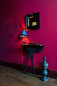 Black console table and mirror on magenta wall
