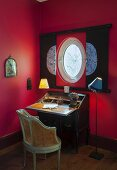 Antique writing desk below porthole window in red wall