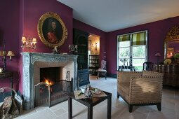 Gilt-framed portrait above fireplace on wall painted purple