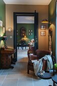 Leather armchair and writing desk in room with walls in shades of green and beige