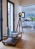 Low sideboard on castors, industrial-style tripod lamp and view into kitchen-dining room