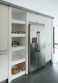 Stainless steel, side-by-side fridge freezer flanked by tall cabinets and open-fronted shelving