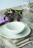 White place setting on linen place mat and sprig of flowers on rustic wooden table