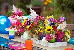 Bunte Becher mit sommerlichen Gartenblumen als Tischdeko