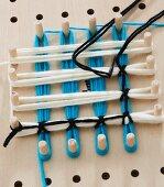 Gelochtes Holzbrett mit umwickelten Stiften aus verschiedenfarbigen Wollfäden