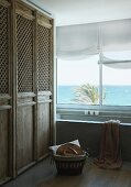Fitted cupboards with rustic wooden doors with mesh panels next to bathtub below window with sea view