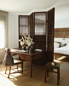 Antique writing desk and chair against wooden screen in front of sleeping area in simple room with well-kept wooden floor