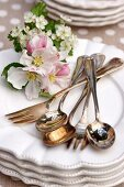 Silver cutlery of flower arrangement on stacked plates