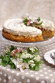 Apple cake with meringue top and fruit tree blossom on polka dot tablecloth outside