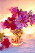 Crystal vase of cosmos and dahlias backlit by candlelight