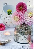Pink dahlias in mercury glass vase on lace doily with teacups in background