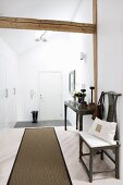 Runner on pale wooden floor, antique chair and console table against wall in hallway