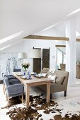 Wooden table, chairs and upholstered bench on animal-skin rug in converted attic