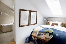 Double bed below skylight and view into bathroom with light beige tiles through open doorway